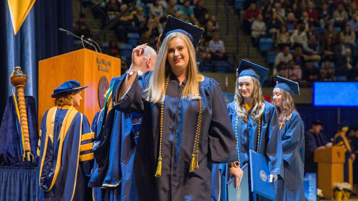 A medical student walks across the stage in December commencement.